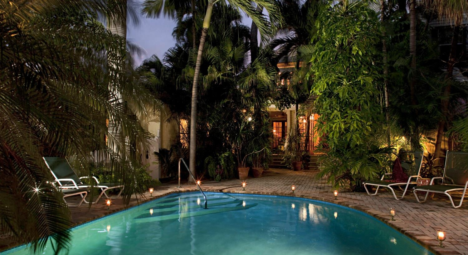 Organic shaped swimming pool with brick pavers at dusk surrounded by romantic lighting and lush tropical greenery