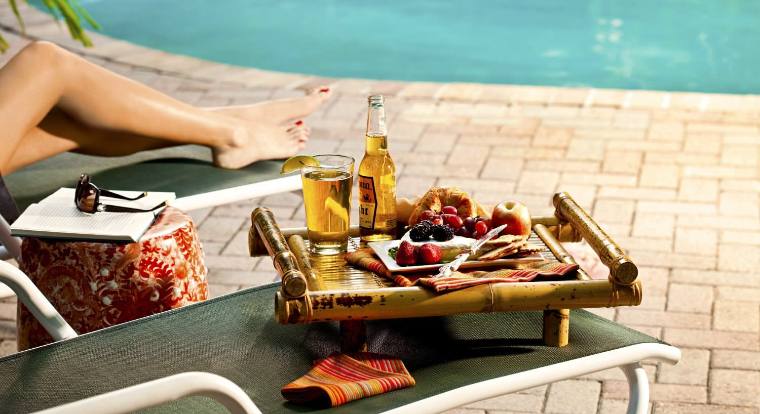Woman on green lounge chair by pool with book and sunglasses. Tray with beer and fruit variety