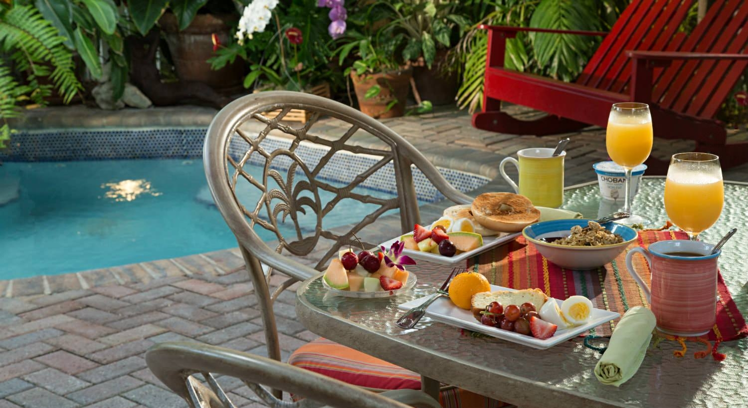 Glass table with breakfast food with red chairs and pool in background