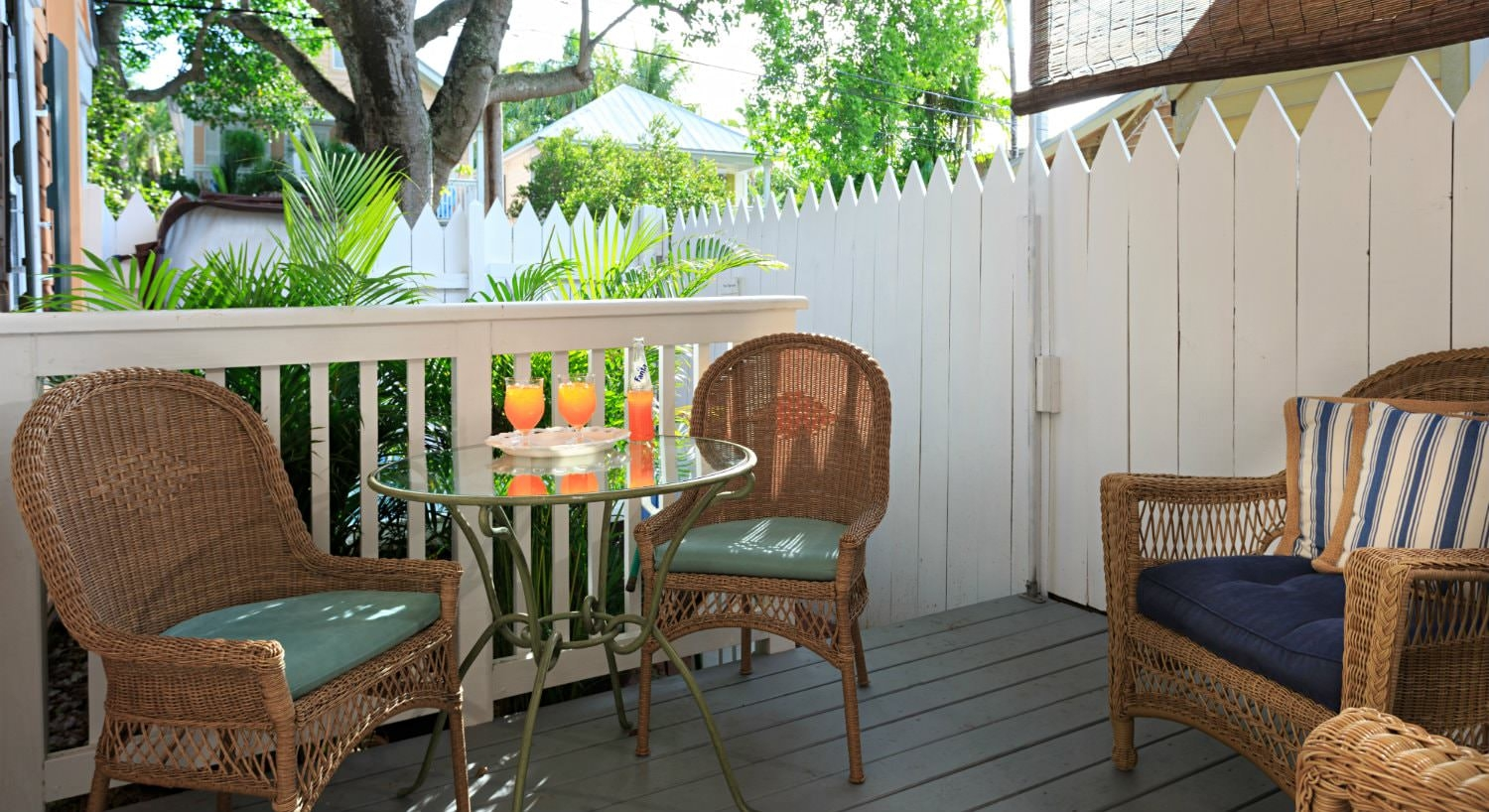 Patio with round glass table with wicker cushioned chairs and wicker chair with blue cushion enclosed by picket fence