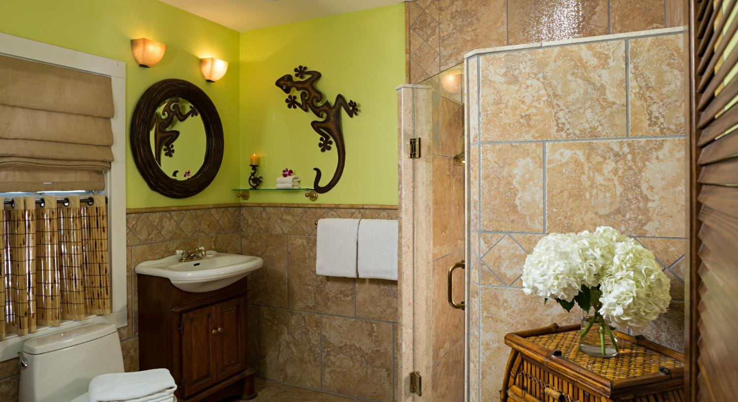 Bright yellow bathroom with gecko figurine on wall with walk in tiled shower with sink with bamboo mirror