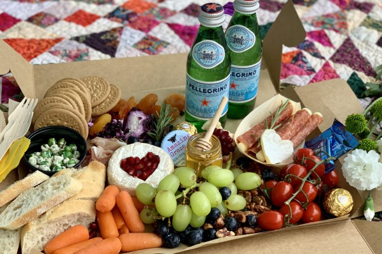 Box on patchwork quilt with 2 green bottles of Pellegrino mineral water and assortment of fruits, vegetables and snacks for picnic.