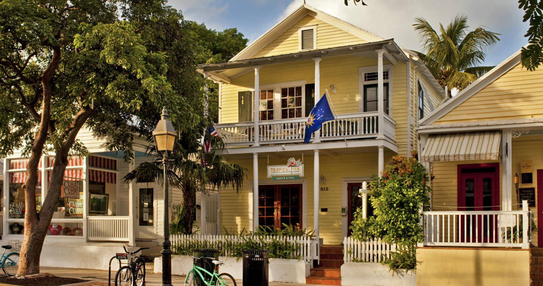 Bright yellow buildings with blue flag flying and green shutters and white picket railings