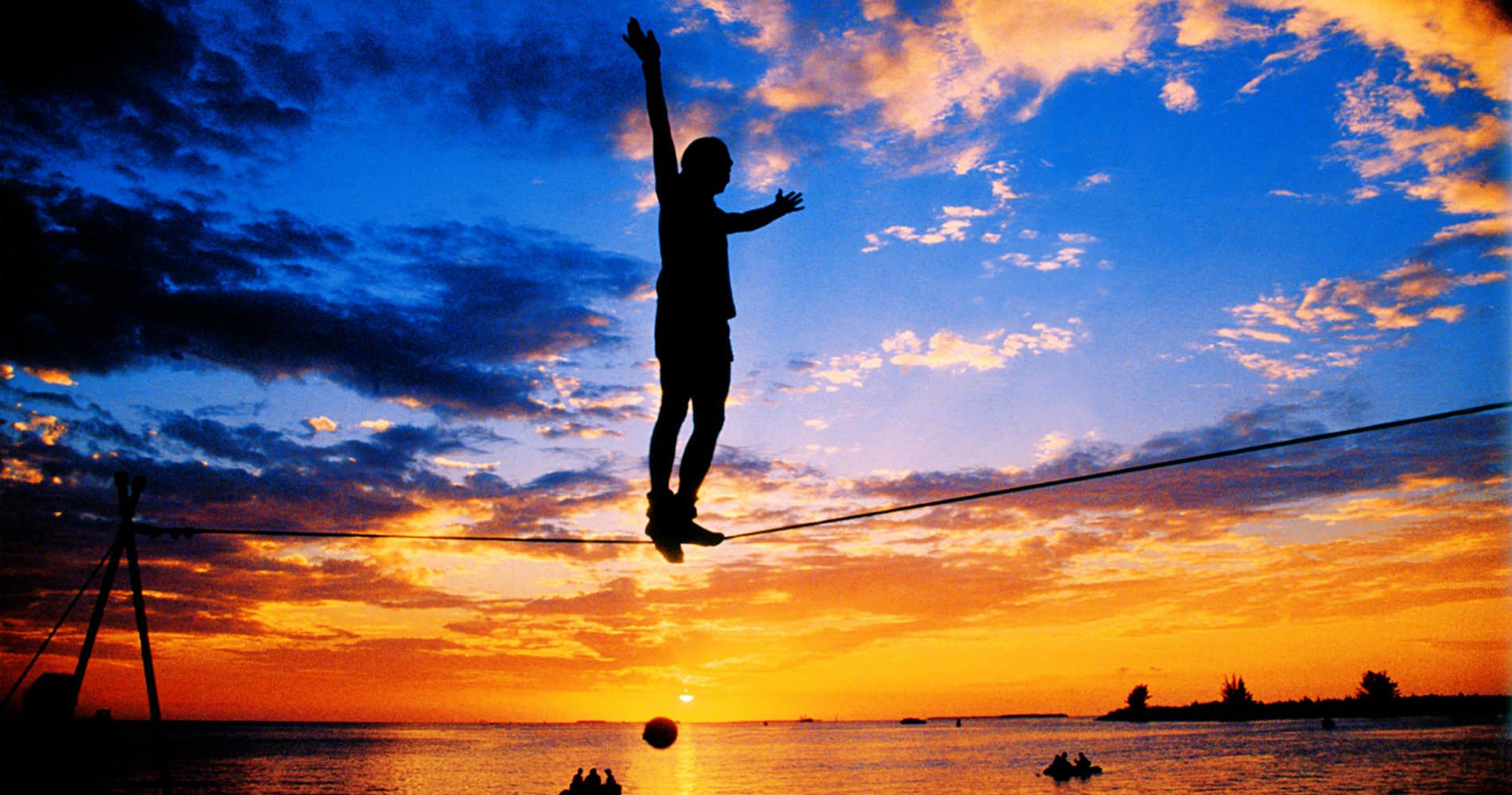 Silhouette figure standing on tightrope over the ocean with sun setting in background
