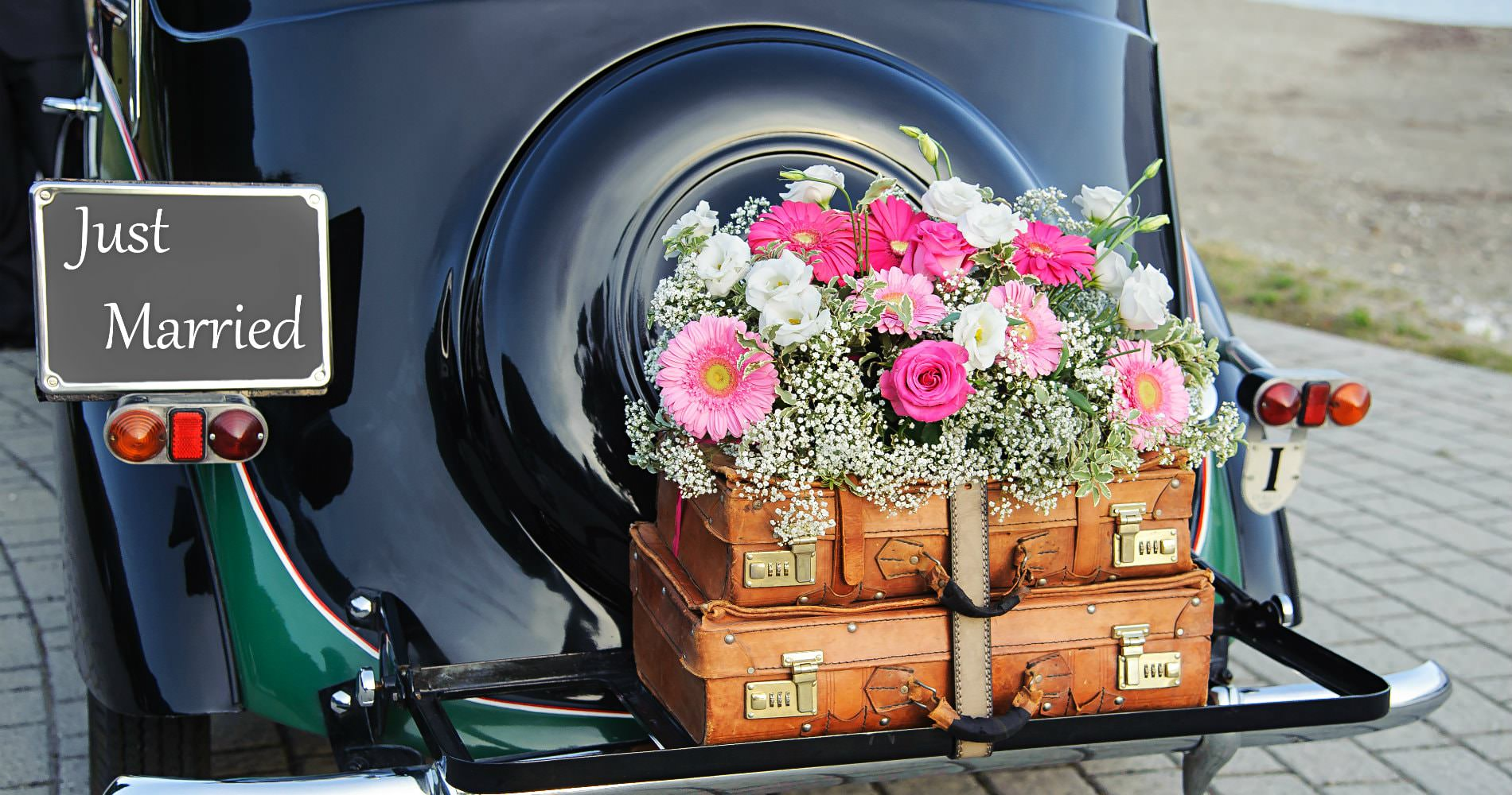 Shiny black antique car with brown trunks, fresh pink flowers, and a Just Married sign on the tailgate