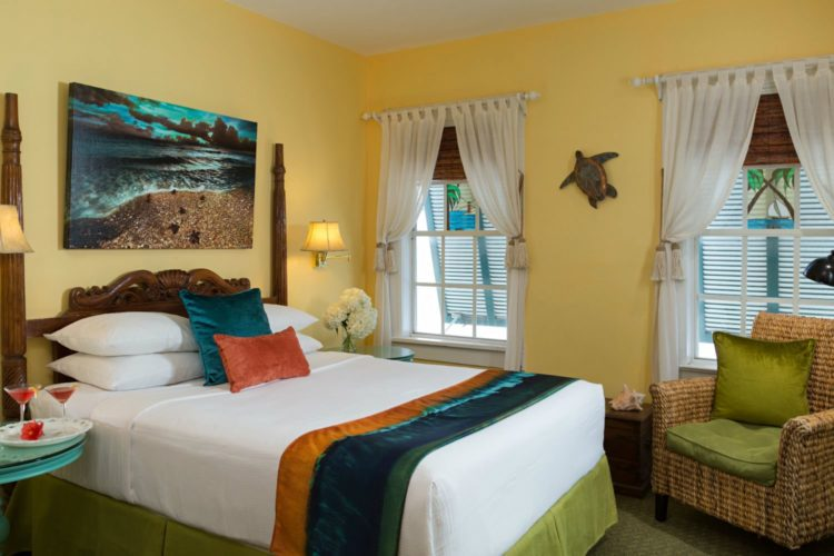Yellow bedroom with twin bed and turtle decoration on wall with end table with champagne flutes with 2 windows