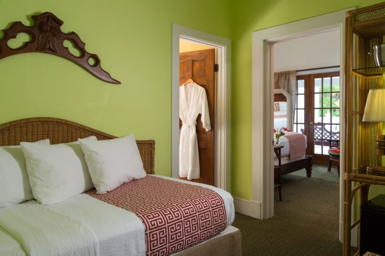 Lime green bedroom with twin bed with connecting bathroom with a separate sitting room connected to patio