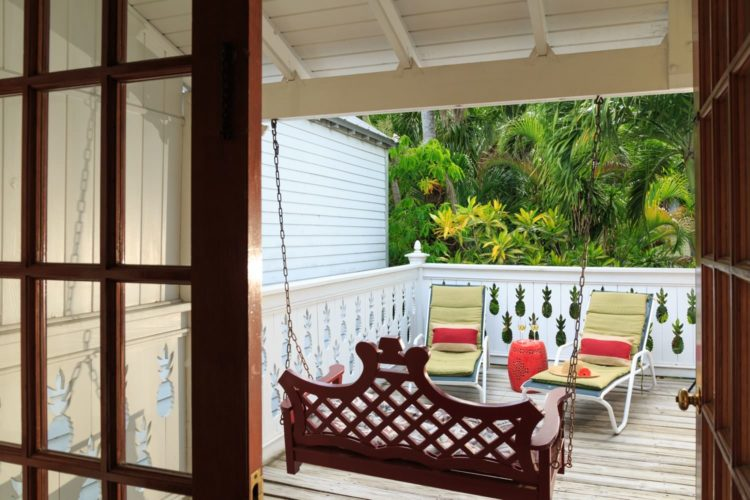 Balcony with lounge chairs with yellow cushions and pillows with hanging porch swing enclosed with white fence
