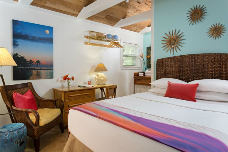Aqua bedroom with wood desk with fish lamp and cushioned wicker chair and ocean painting with wood decorations above bed