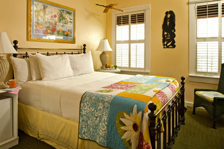 Mustard yellow bedroom with painting above bed and patchwork quilt with iron head and foot boards with 2 windows