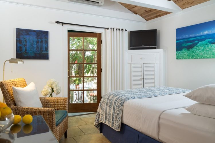 White painted bedroom with door leading to patio with white cabinet in corner with television and cushioned wicker chair