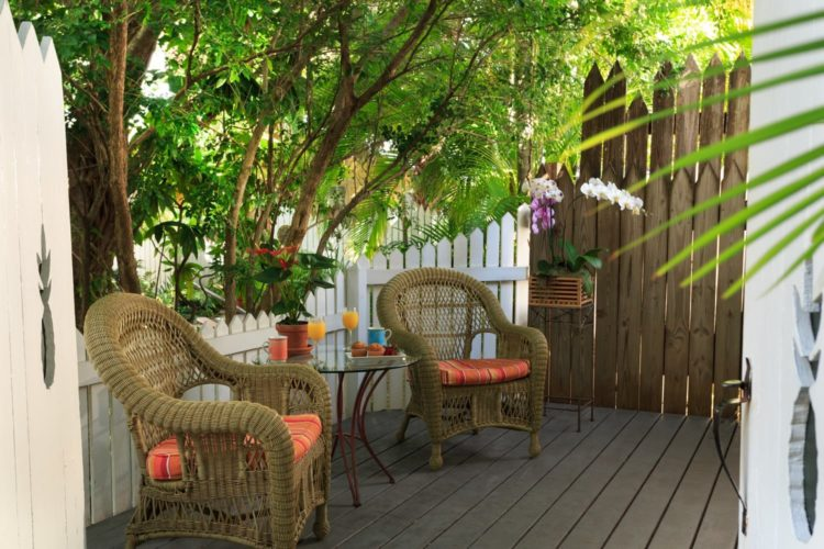 Wood deck with cushioned wicker chairs and round glass table surrounded by white and brown picket fence