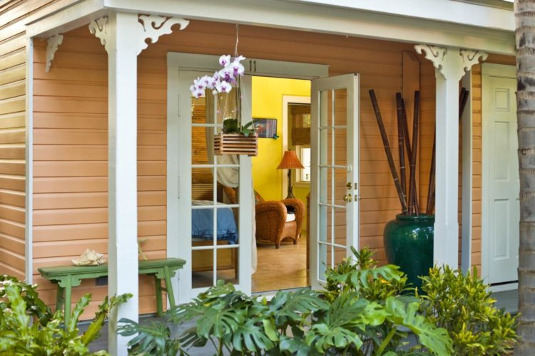 Patio with opened white glass door leading into yellow sitting rom with hanging planter on patio