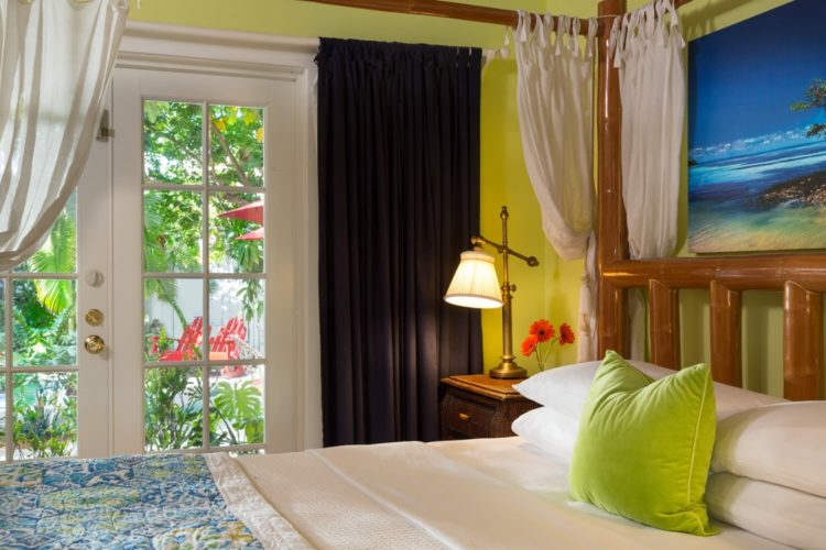 Bright yellow bedroom with 4 poster canopy bed with glass door leading to garden with red wooden chairs