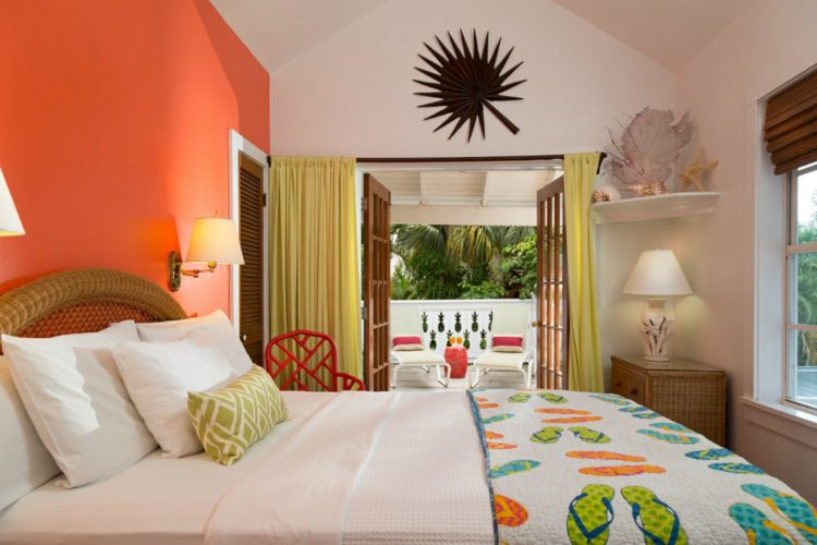 Bed with comforter with flip flops entered onto enclosed patio with cream lounge chairs with seashells on shelf in corner