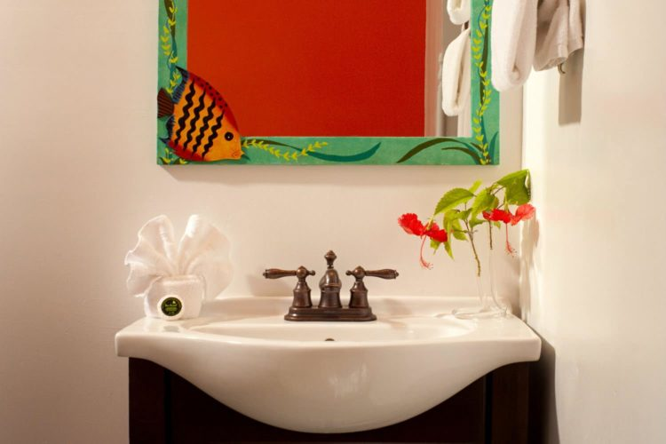 Sink with antique brass fixtures and mirror painted with ocean scene (fish in corner) and towels hanging on wall