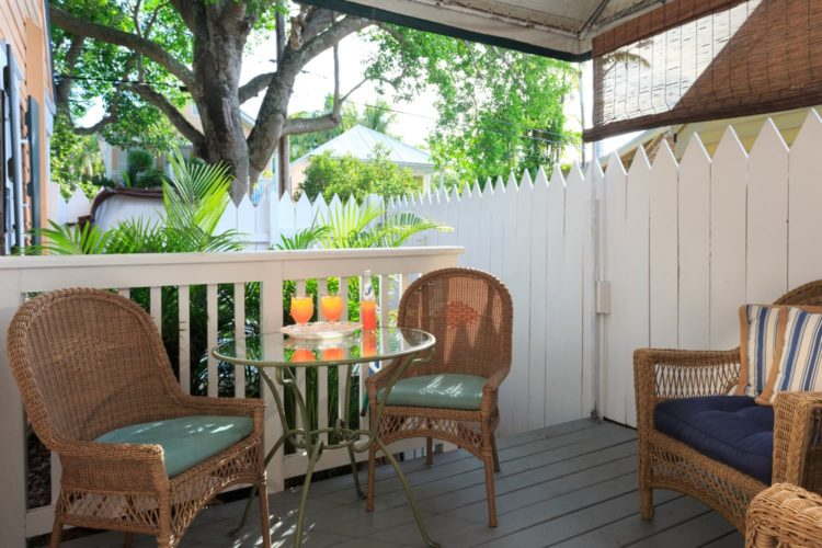 Covered patio with round glass table with cushioned wicker chairs surrounded by white picket fence