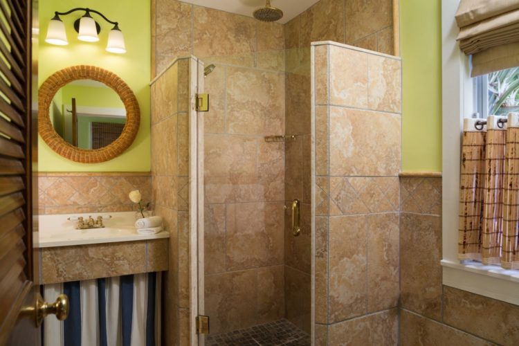 Yellow bathroom with glass tiled walk in shower with separate sink and mirror and window with bamboo curtains and blind