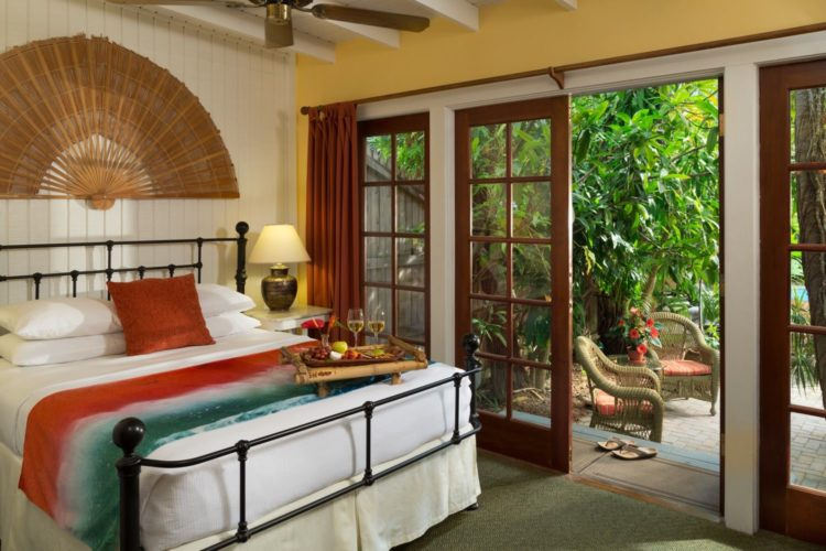 Bedroom with queen bed and wicker fan decoration with ceiling fan and glass doors leading to patio with wicker chairs