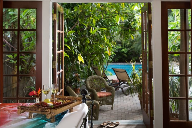 View from bedroom leading to pool with lounge and wicker chairs surrounded by dense greenery