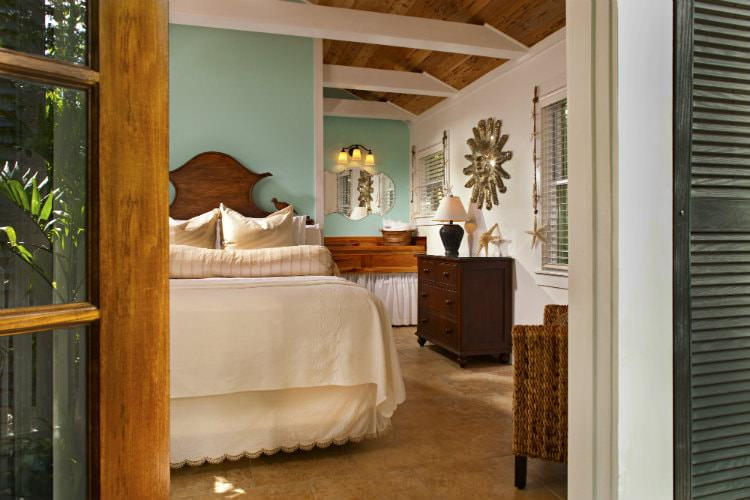 Mint green bedroom with separate room with wood countertop and end table with lamp and wicker chair