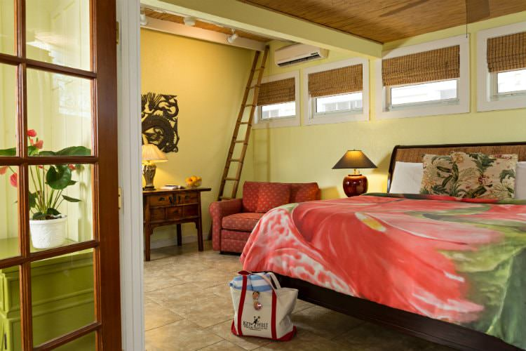 Canary yellow room with loft and king size bed with peach and green bedspread and end table with lamp