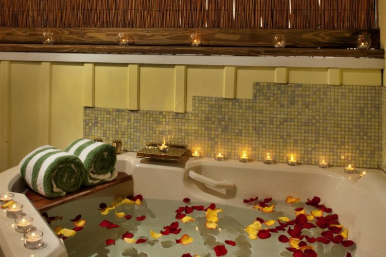 Large jacuzzi tub with red and yellow flower petals in water surrounded by small lit candles for mood lighting