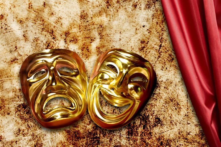 2 shiny gold masks (1 smiling and 1 frowning) on brown and white blanket with red silky material next to it