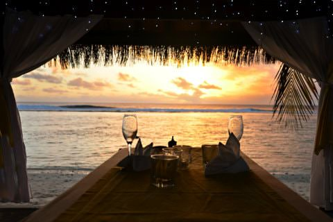 Straw hut with 2 wine glasses on table next to ocean with sun setting in background