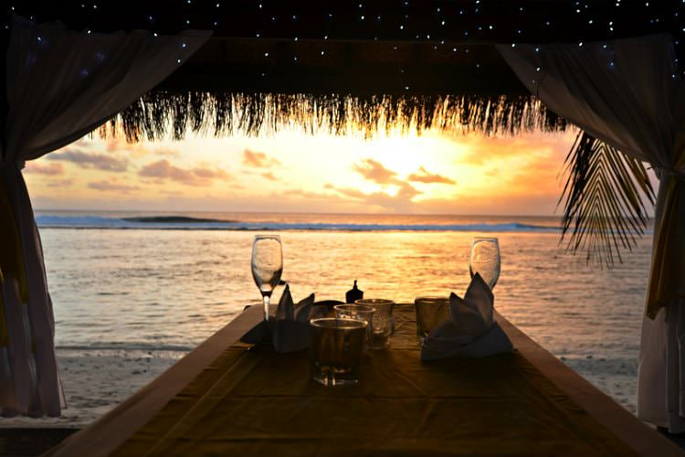 traw hut with 2 wine glasses on table next to ocean with sun setting in background