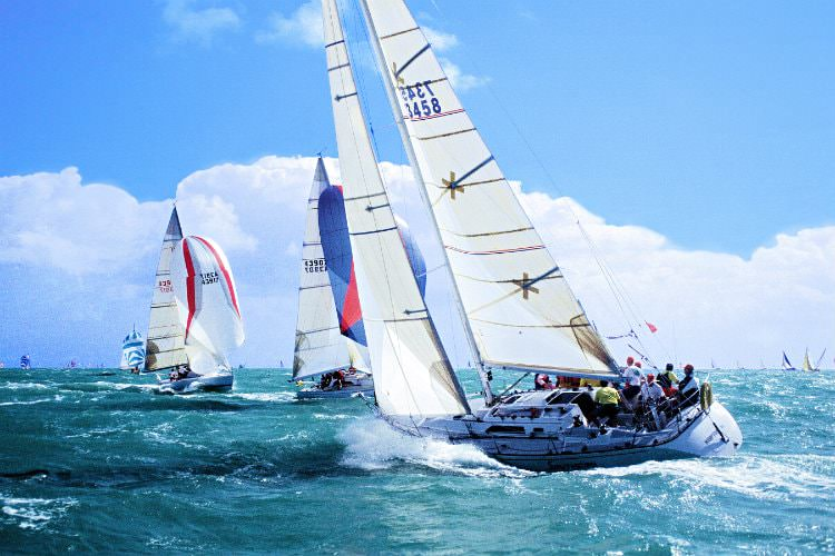 A group of sailboats on the choppy ocean waters with bright blue sky and fluffy clouds in background