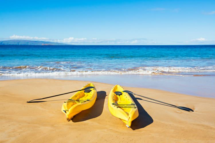Two yellow plastic kayaks on sandy beach with blue ocean