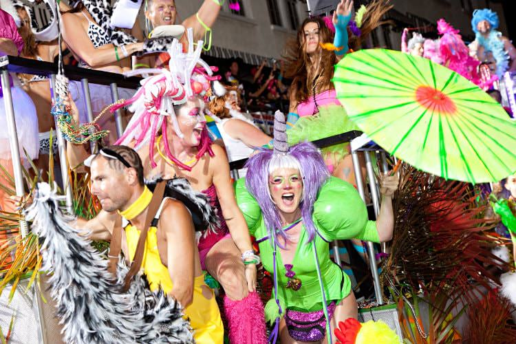 People dressed up in bright costumes with black railing in background dancing at a festive celebration