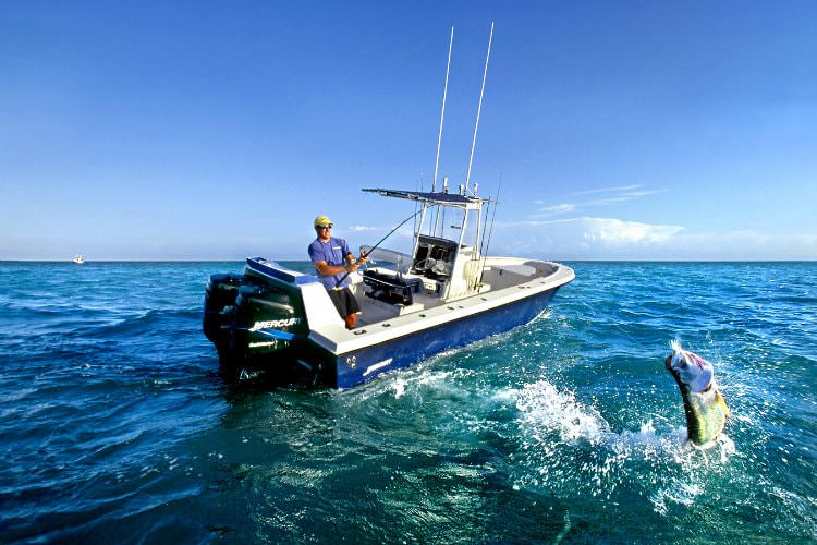 Man fishing on motor boat in middle of ocean with 1 fish on line