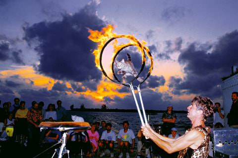 Group of people on beach watching flaming hoop male performer at dusk