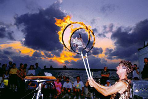 Group of people on beach watching flaming hoop male performer at dusk