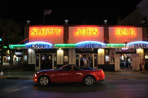 Shiny red convertible on the street in front of Sloppy Joe's Bar at night