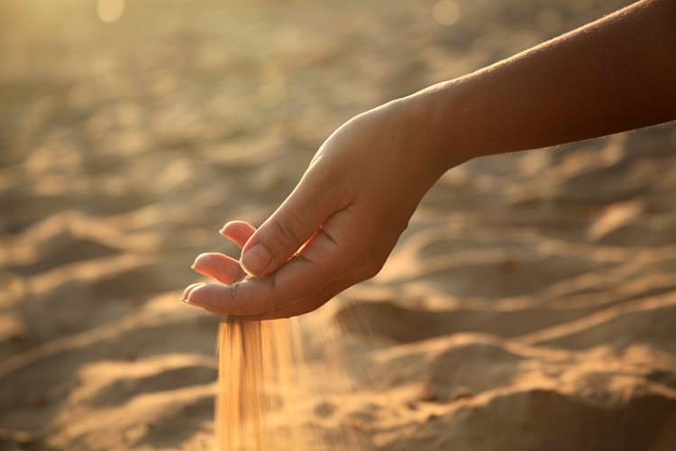 Woman's arm on a sunny day with sand sifting through bent hand