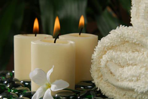 3 burning cream candles next to cream fluffy towels with Lily in front sitting on shiny stones