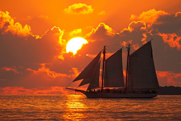 Sailboat on ocean with sun setting in background