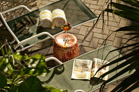 Mesh lounge chairs with yellow and white towels and magazine on chair with table containing champagne flute