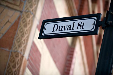 Black and white rectangular street sign Duval street next to brick building